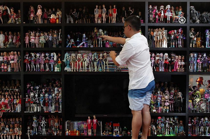 Doll collector Jian Yang stands on a stool as he arranges part of his collection at his home in Singapore on Monday, Sept 2, 2013. -- PHOTO: REUTERS
