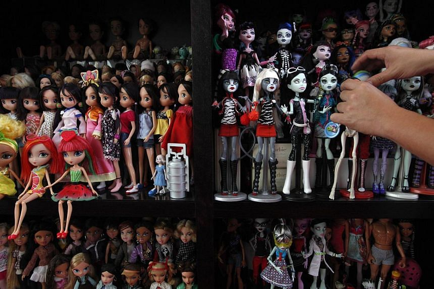 Doll collector Jian Yang arranges his Monster High dolls among other dolls at his home in Singapore on Monday, Sept 2, 2013. -- PHOTO: REUTERS