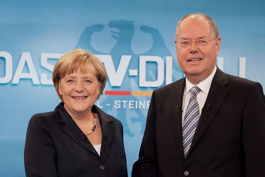 German Chancellor Angela Merkel (left) and her challenger Peer Steinbrueck of the SPD shake hands prior to a television debate in Berlin on Sunday, Sept 1, 2013, ahead of the General election taking place on Sunday, Sept 22, 2013. A TV clash bet