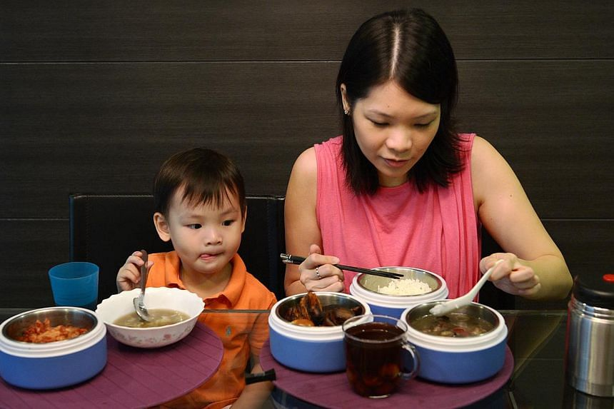 Madam Charlene Wee and her older son Caleb, three, tucking into a meal similar to those she received during her confinement last December after giving birth to her second son.
