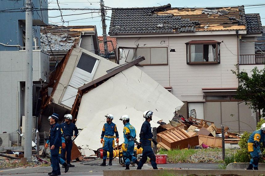 Firefighters and policemen check damaged houses after a tornado tore though Koshigaya in Saitama prefecture, suburban Tokyo on Monday, Sept 2, 2013. -- PHOTO: AFP
