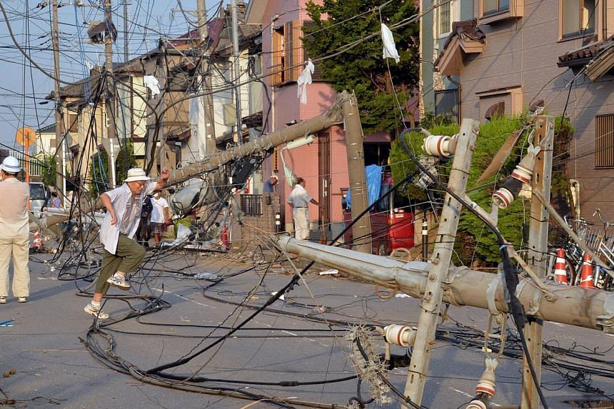 Downed electricity poles and wires cover a street next to damaged houses after a tornado tore though Koshigaya in Saitama prefecture, suburban Tokyo on Monday, Sept 2, 2013. -- PHOTO: AFP