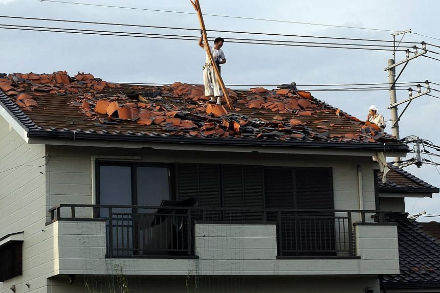 Men remove debris from the roof of a house damaged by a tornado in Koshigaya, north of Tokyo on Monday, Sept 2, 2013. -- PHOTO: REUTERS