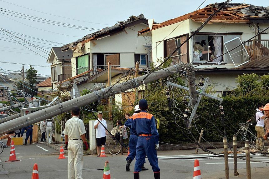 Local residents look at downed electricity poles and damaged homes after a tornado tore though Koshigaya in Saitama prefecture, suburban Tokyo on Monday, Sept 2, 2013. -- PHOTO: AFP