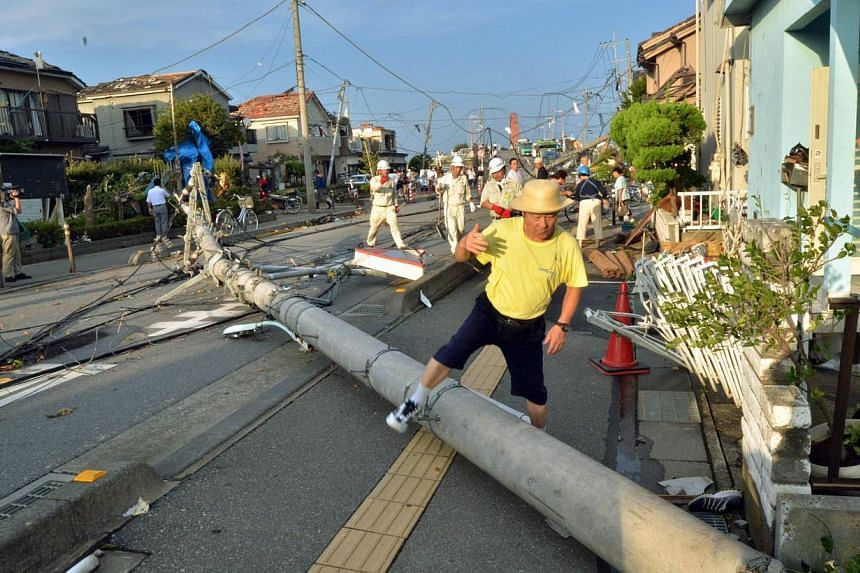 A man steps over a downed electricity pole fallen across a street as people clean up debris after a tornado tore though Koshigaya in Saitama prefecture, suburban Tokyo on Monday, Sept 2, 2013. -- PHOTO: AFP
