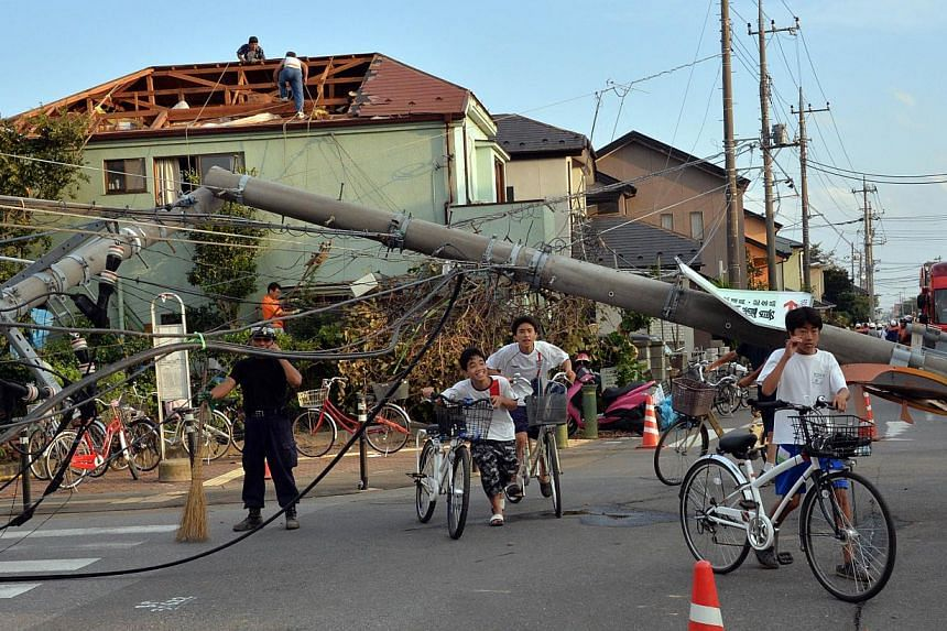 Local residents walk under collapsed electricity poles after a tornado tore though Koshigaya in Saitama prefecture, suburban Tokyo on Monday, Sept 2, 2013. -- PHOTO: AFP