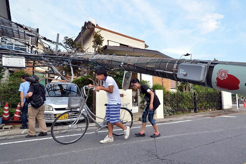 Local residents walk under a downed electricity pole after a tornado tore though Koshigaya in Saitama prefecture, suburban Tokyo on Monday, Sept 2, 2013. -- PHOTO: AFP