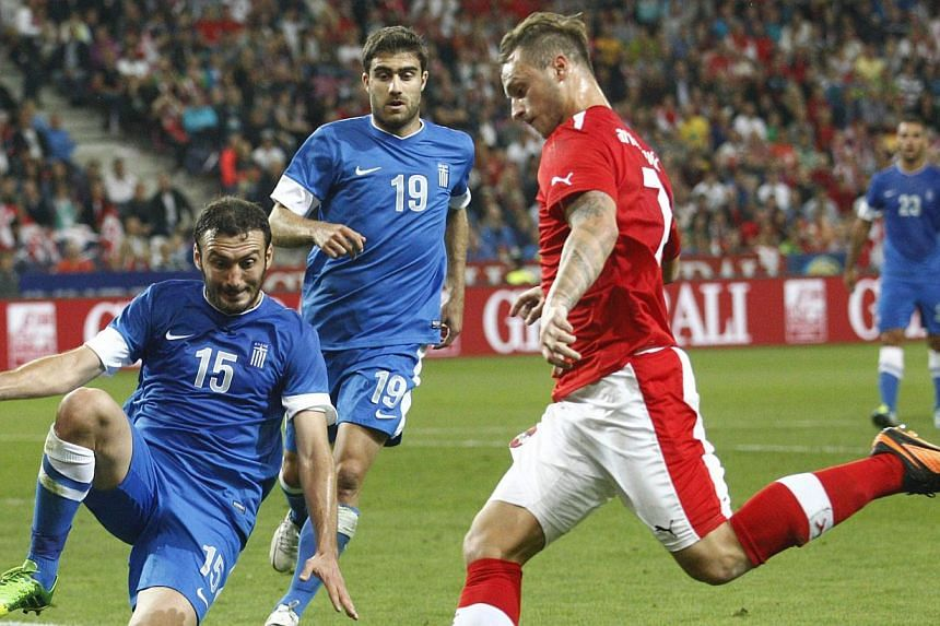Austria's Marko Arnautovic (right) challenges Greece's Vassilis Torosidis (15) during their international friendly soccer match in Salzburg, Aug 14, 2013. Arnautovic has joined Stoke City from Werder Bremen on a four-year contract, the English P