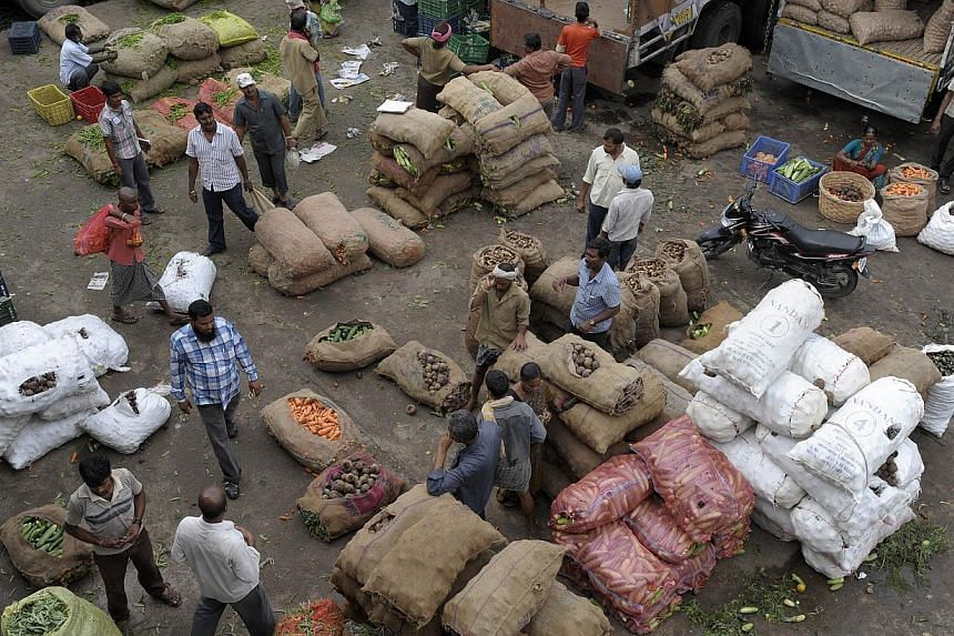 Indian vendors negotiate prices at a vegetable wholesale market in Hyderabad on June 12, 2013. India's upper house of parliament on Monday approved a US$20 billion (S$25.5 billion) scheme to distribute subsidised wheat and rice to 800 million people,