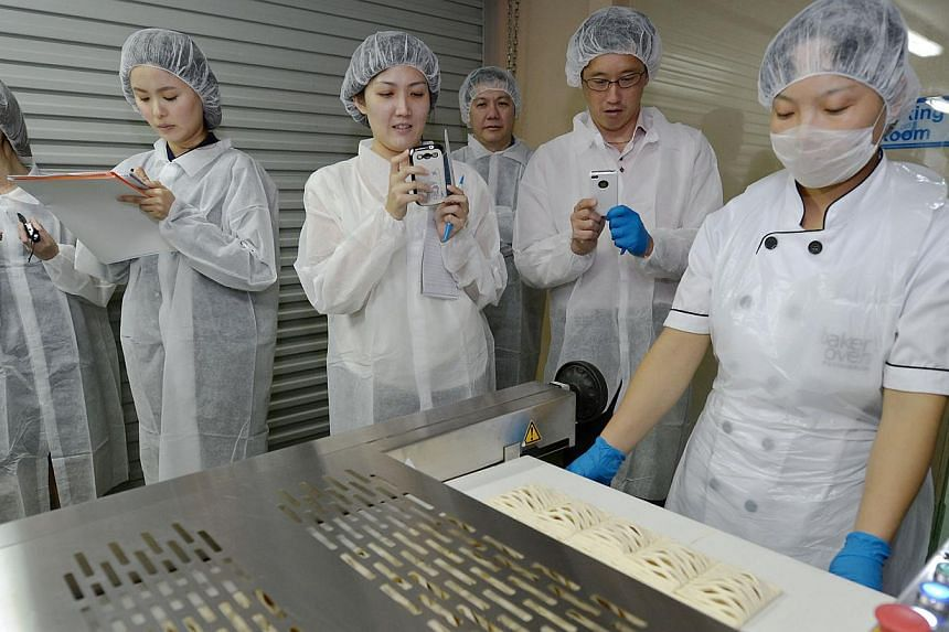 Minister of State for Trade and Industry Teo Ser Luck (2nd from right) snaps a shot of the final product from Baker's Oven Pattisieries turnkey line that integrated various bakery equipment into a single, fully automated production line on August 27,