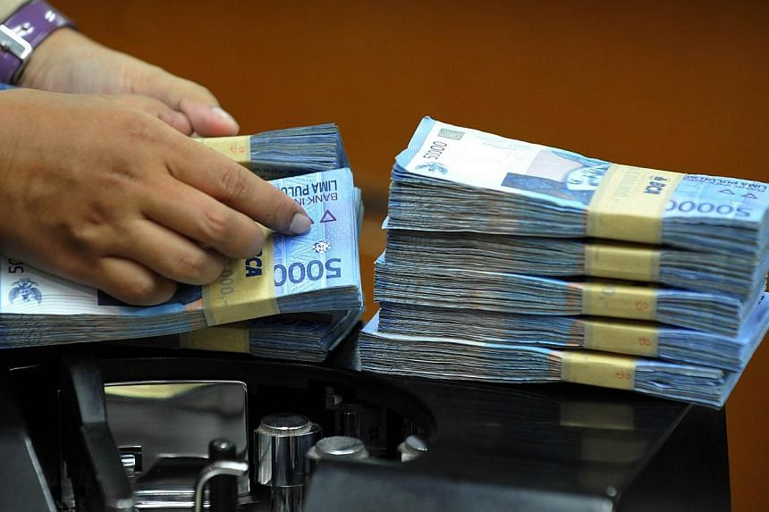 This picture taken in Jakarta on Aug 28, 2013 shows an Indonesian clerk handling stacks of Indonesian rupiah notes at a money changer office in Jakarta. Singapore's economy is likely to be adversely affected by a looming growth slowdown in Indonesia
