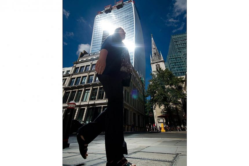 """A woman walks through the shaft of intense sunlight reflected from the glass windows of the new """"Walkie Talkie"""" tower in central London on August 30, 2013.The skyscraper's developers said they were seeking to rectify the problem which the"""