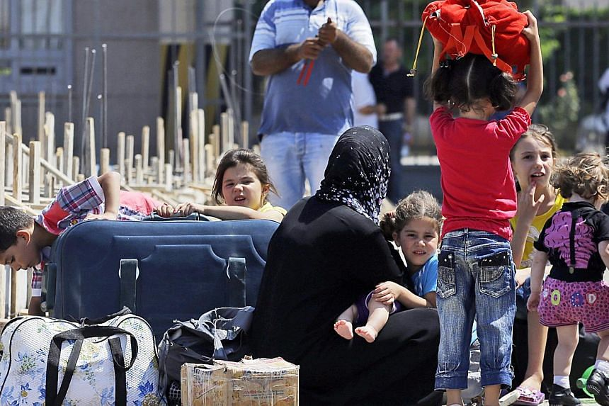 Syrian refugees arrive at the Turkish Cilvegozu gate border, Monday, Sept 2, 2013. Italy warned on Monday the European Union lacks an adequate approach for the refugee problem that will worsen in case of an international intervention in Syria.-
