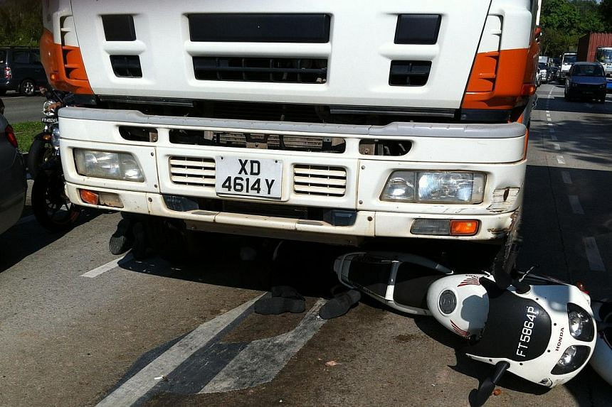 A motorcyclist was pinned under a tipper truck after an accident occured near the junction of Yishun Ave 1 and Ave 2 on Tuesday morning. Officers from the Singapore Civil Defence Force (SCDF) had to jack up the truck to remove the motorcyclist. -- PH
