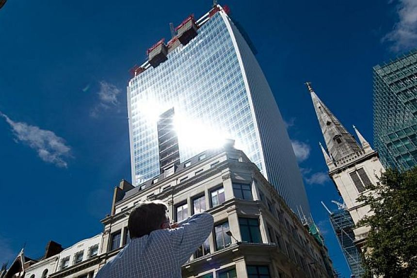 A man reacts to a shaft of intense sunlight reflected from the glass windows of the new Walkie Talkie tower in central London on Aug 30, 2013. A motorist said intense sunlight reflected from the Walkie Talkie warped his Jaguar which he had parked acr