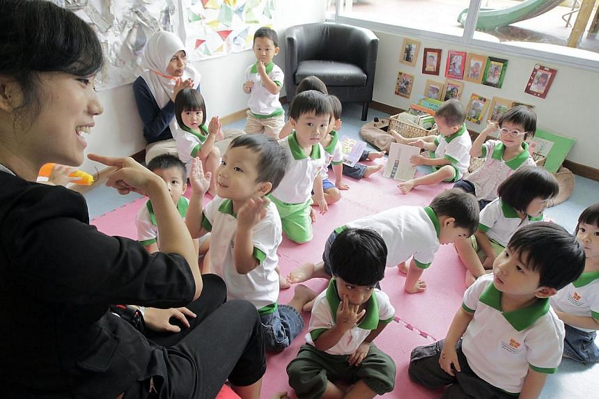 A teacher leading a group of toddlers in a music and movement class at pre-school The Caterpillar's Cove on April 18, 2011. A new mentoring starter kit for pre-school teachers was launched on Tuesday. -- ST FILE PHOTO: NEO XIAOBIN