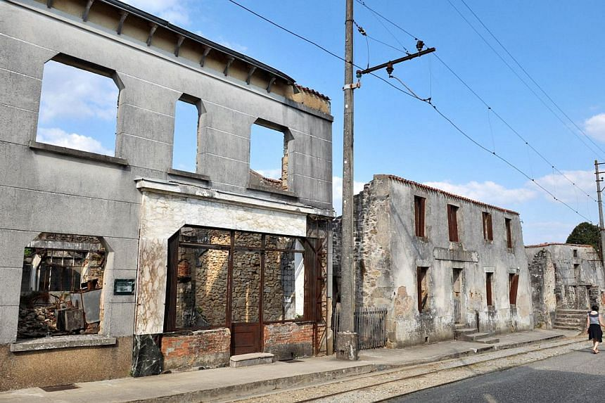 People visit on Aug 30, 2013 the martyr village of Oradour-sur-Glane, central France, where 642 citizens including 500 women and children were killed locked up in a church intentionally set on fire by a SS division on June 10, 1944. German President
