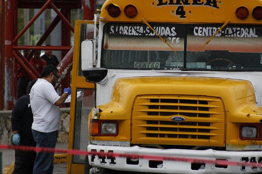 """In this Aug 29, 2013 photo, forensic workers examine the scene where a bus driver was allegedly killed by a self-styled """"bus driver hunter,"""" in Ciudad Juarez, Mexico. Authorities are seeking a woman accused of killing two bus drivers in northern Mexi"""