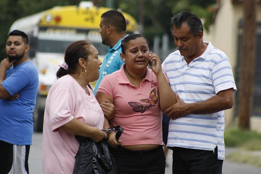 """In this Aug 28, 2013 photo, an unidentified relative is escorted from the scene where a bus driver was allegedly killed by a self-styled """"bus driver hunter,"""" in Ciudad Juarez, Mexico. Mexican prosecutors said on Monday, Sept 2, 2013, they are investi"""
