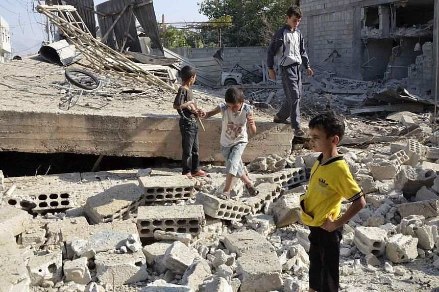Boys walk on the rubble of a building hit by what activists said was shelling by forces loyal to Syria's President Bashar al-Assad, in the Duma neighbourhood of Damascus on Wednesday, Sept 4, 2013.Syria's Deputy Foreign Minister said on Wednesd