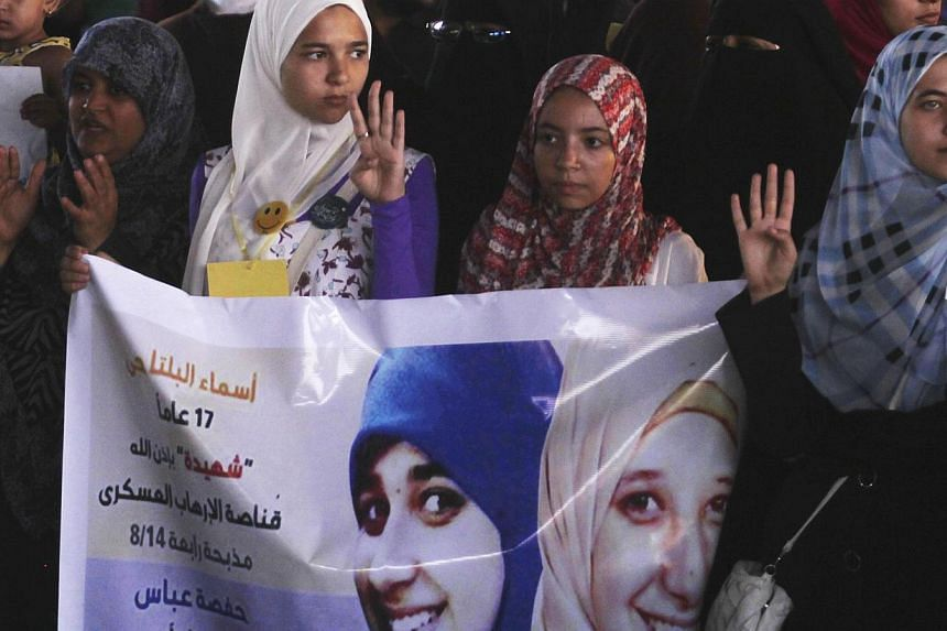 """Members of the Muslim Brotherhood and supporters of ousted Egyptian President Mohamed Mursi rally against the military and interior ministry, as they show the """"Rabaa"""" or """"four"""" gesture, in reference to the police clearing of Rabaa al-Adawiya protest"""