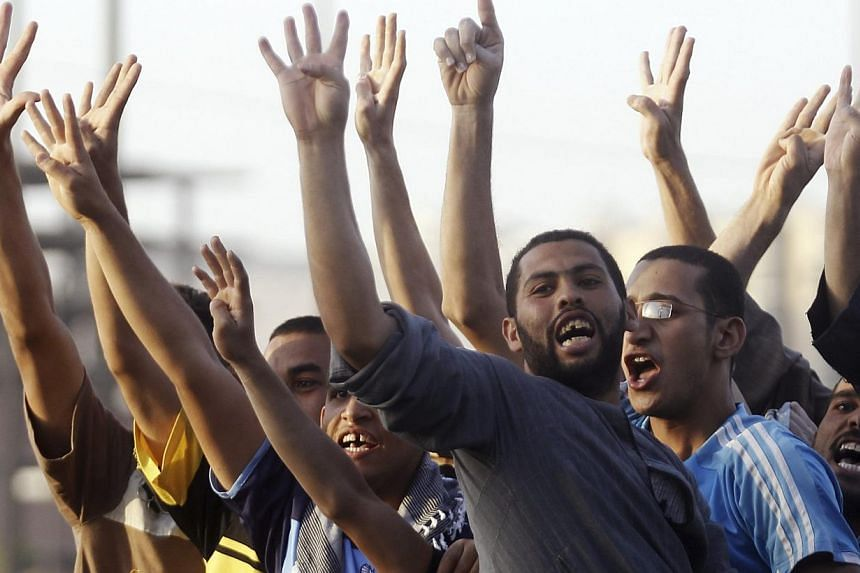 "People show the ""Rabaa"" or ""four"" gesture, in reference to the police clearing of Rabaa al-Adawiya protest camp on Aug 14, during a traffic jam as members of the Muslim Brotherhood and supporters of ousted Egyptian President Mohamed Mursi stage a pro"