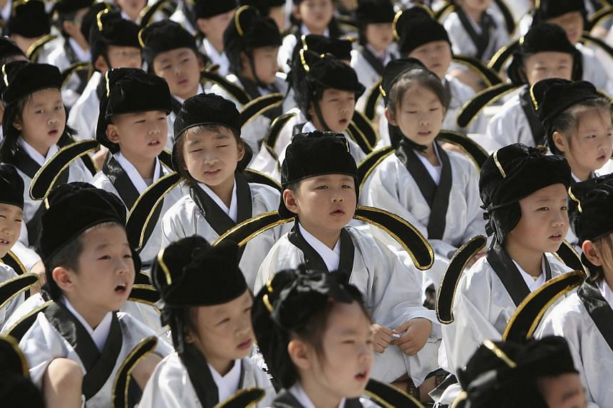 Pupils in traditional costumes attend a ceremony at the Confucius temple in Nanjing, Jiangsu province, Sept 1, 2013. Beijing is making another big push for linguistic unity as research has shown that more than 400 million Chinese are unable to speak