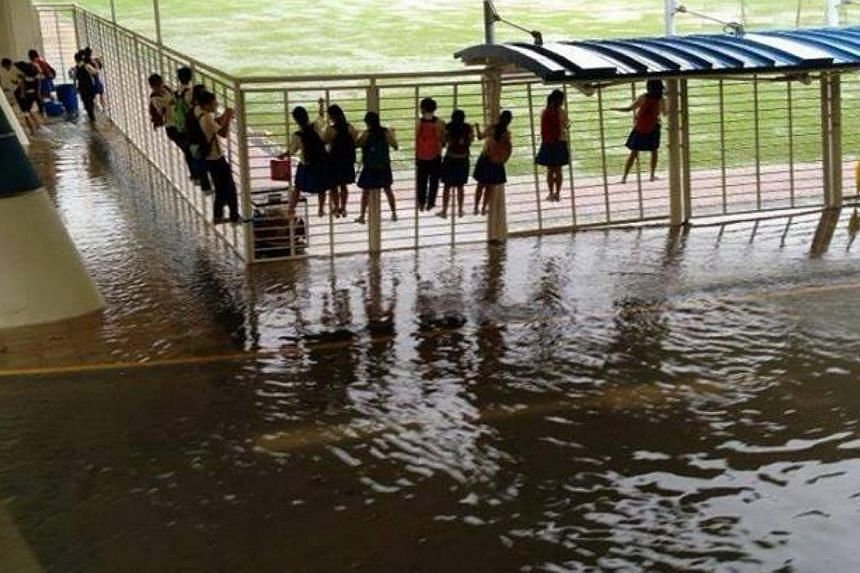 A photograph of students clinging on to a fence to avoid a flooded section of their school has also been making its rounds on the Internet. It is understood that the picture was taken at Fairfield Methodist Secondary. -- PHOTO: INTERNET