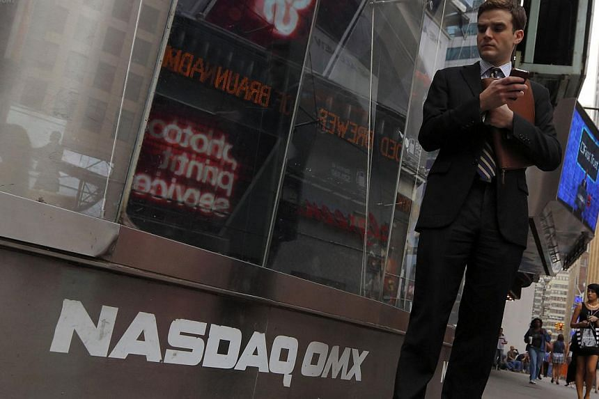 A man stands next to the Nasdaq MarketSite in New York on Aug 23, 2013. Nasdaq OMX Group said the system at the centre of the Nasdaq exchange's three-hour trading halt on Aug 22 had a six minute outage on Wednesday for a small number of stock symbols
