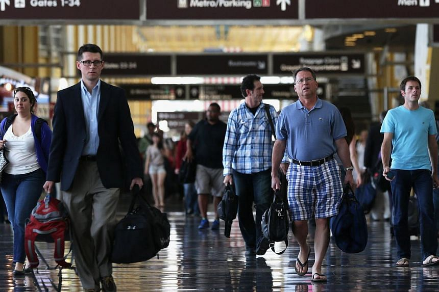 Air travelers walk in a terminal of the Ronald Reagan National Airport August 30, 2013 in Arlington, VA. According to an AAA forecast, about 34.1 million Americans will travel at least 50 miles from home over the Labor Day long weekend, the highest f