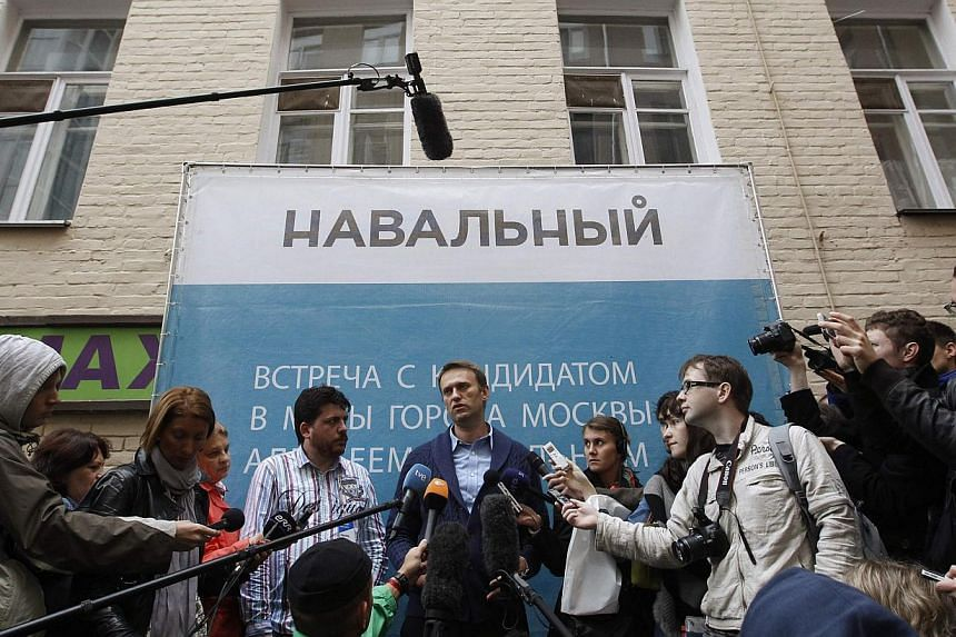 Mr Navalny (centre) talks to the media outside his campaign headquarters in Moscow on Sept 4, 2013. Mr Navalny on Sunday takes on a Kremlin-backed incumbent in a hotly contested Moscow mayoral poll, the first time the Kremlin has allowed a bitter opp