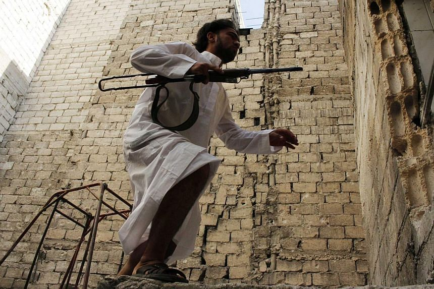 A Free Syrian Army fighter carries his weapon as he moves between buildings in the Aleppo district of Salaheddine on Sept 4, 2013. Washington is weighing expanding support for Syrian rebels by having the Pentagon take charge of arming the opposition