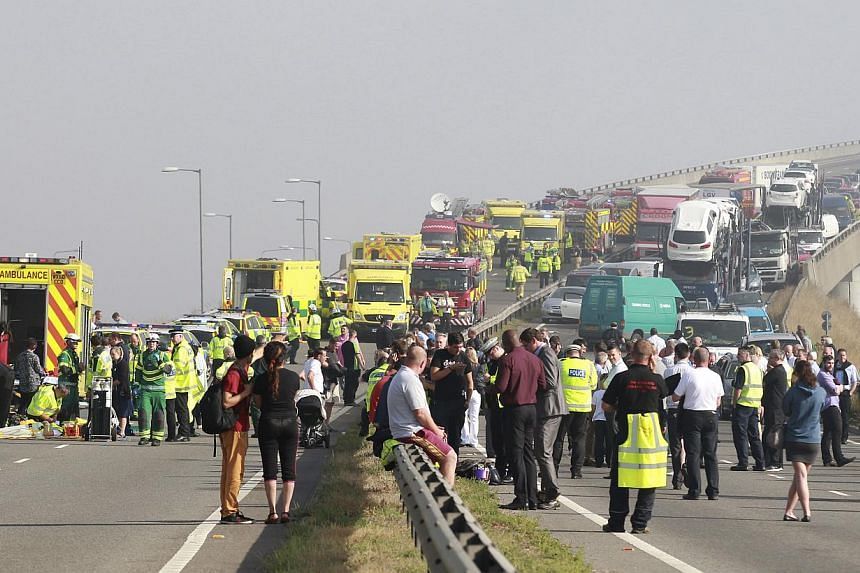 Emergency services treat the injured (left) as traffic is stopped on the London bound carriageway of the Sheppey Bridge Crossing near Sheerness in Kent, south England,following a multi-vehicle collision on Thursday, Sept 5, 2013. -- PHOTO: AP