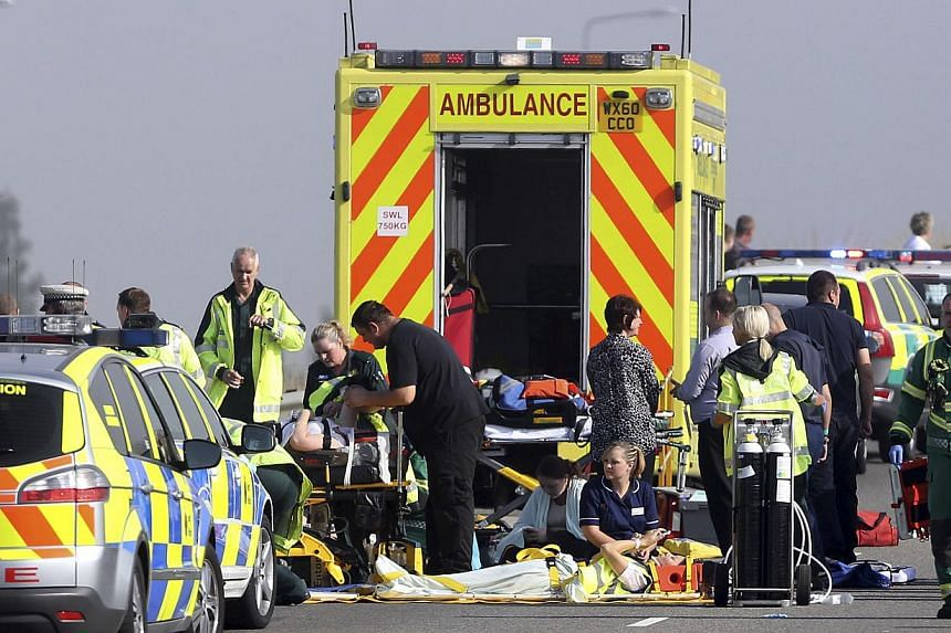 Injured people are treated on the road carriagewayat the scene of the Sheppey Bridge Crossing near Sheerness in Kent, south England,following a multi-vehicle collision on Thursday, Sept 5, 2013. -- PHOTO: AP