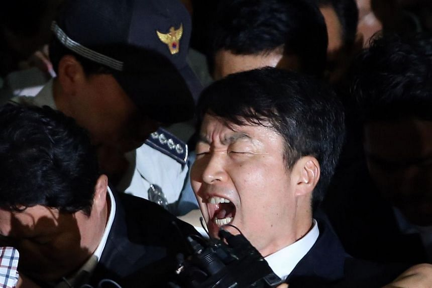 South Korea's United Progressive Party legislator Lee Seok Ki (centre) shouts as security agents escort him into a van to a prison, at a police station in Suwon, south of Seoul on Thursday, Sept 5, 2013.A South Korean leftist lawmaker was forma