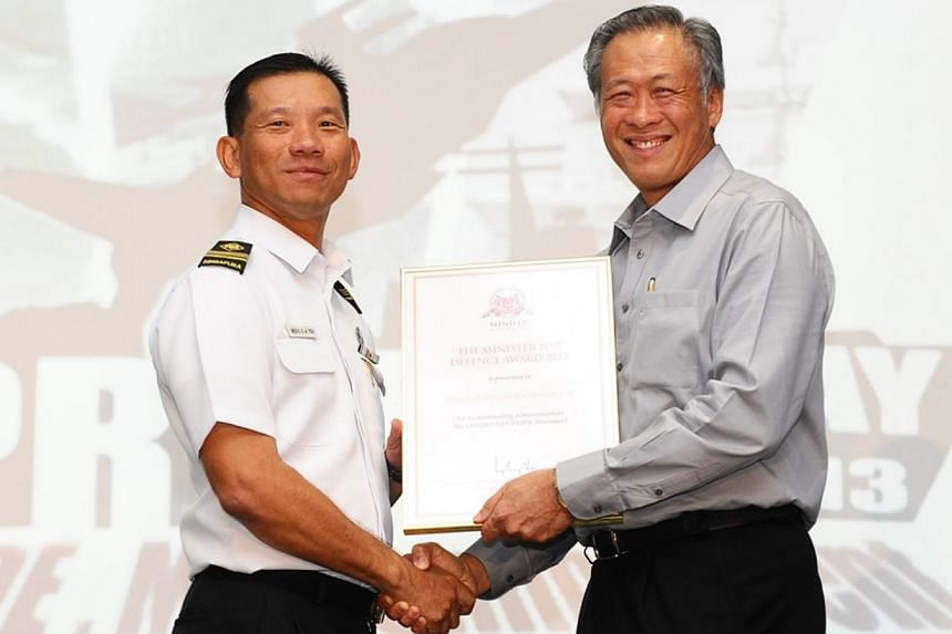 Minister for Defence Ng Eng Hen (right) gives out the prestigious Minister for Defence Award to ME6 Teh Chong Ann, Commander of the Force Readiness Squadron. Dr Ng handed out 21 awards to individuals, groups, and units from the Ministry of Defen