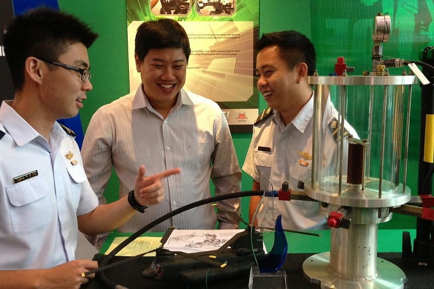 (From right) ME4 Ng Wei Rong, 25, 1SG (NS) Seah Boon Ping, 34, and ME2 Seah Jun Yao, 28, with their modified Chinook Rotor Head Seal Pressure tester. -- ST PHOTO: YEO SAM JO