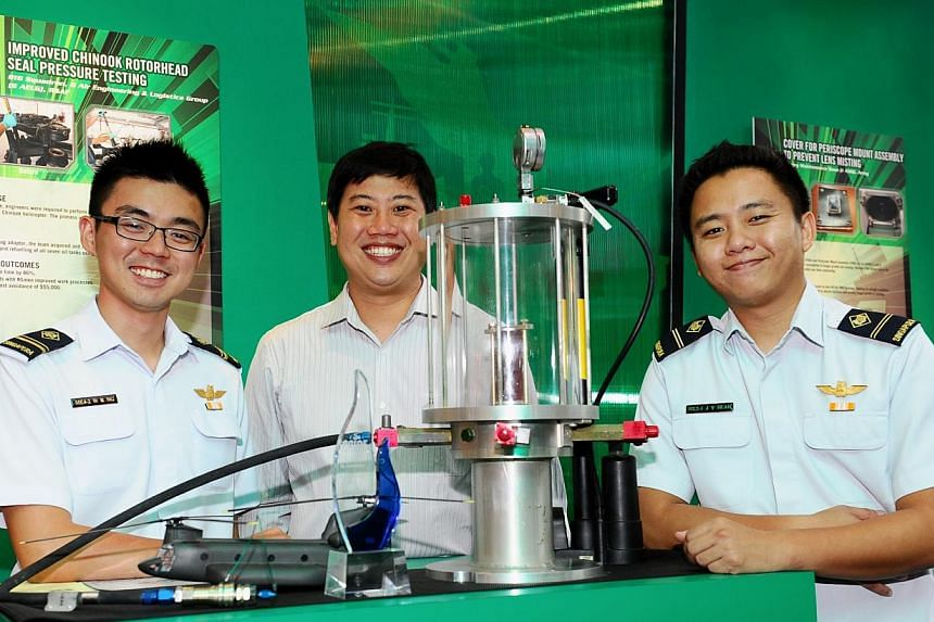 (From right) ME4 Ng Wei Rong, 1SG (NS) Seah Boon Ping and ME2 Seah Jun Yao with their modified Chinook Rotor Head Seal Pressure tester. -- PHOTO: MINDEF