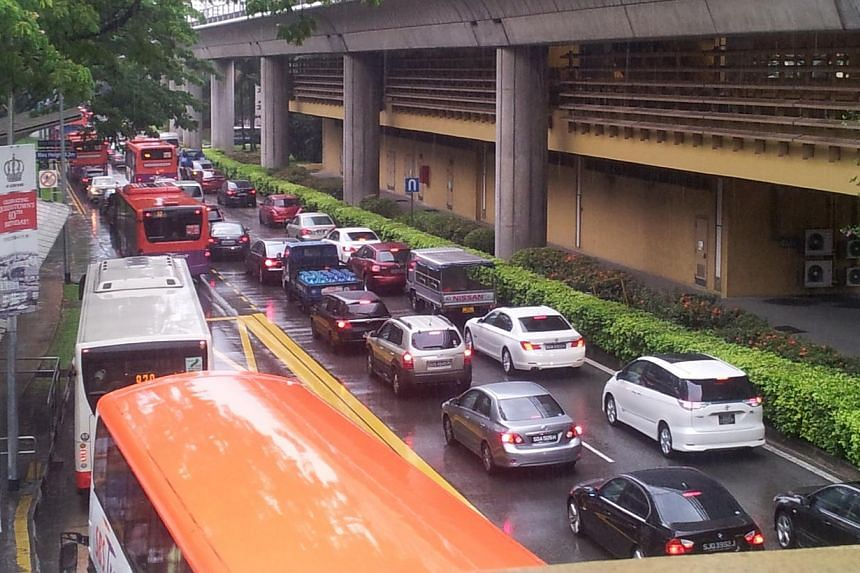Traffic at a standstill near Commonwealth MRT. Many parts of Singapore reported moderate to heavy thundery showers on Thursday morning, resulting in flash floods and traffic jams in some areas. -- ST PHOTO: RACHEL AU-YONG