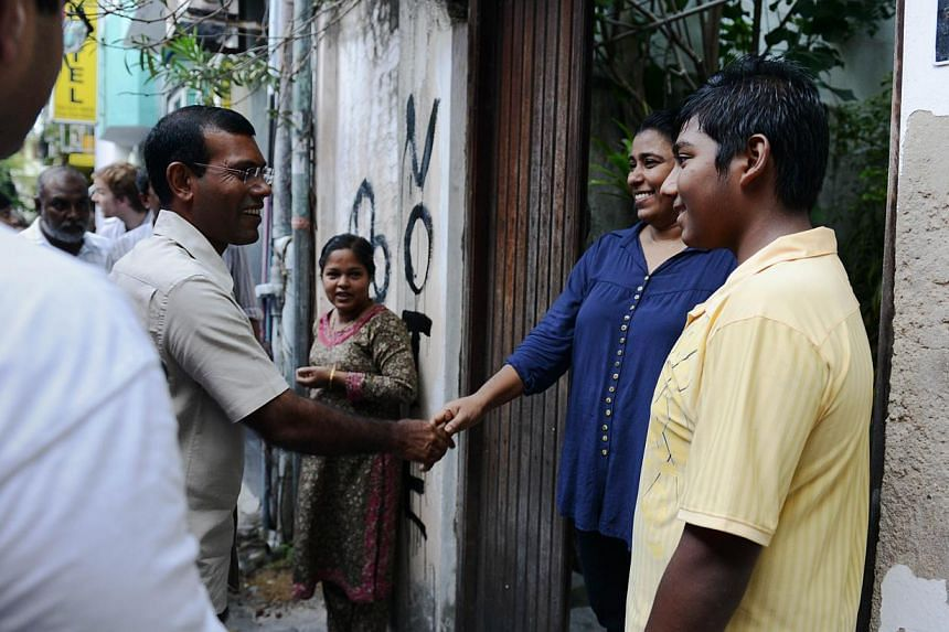 Former Maldivian president and presidential candidate Mohamed Nasheed (second from left) greeting residents of Male while he toured a neighborhood of Maldives' capital on September 4, 2013, three days before some 139,000 voters will go to the polls t