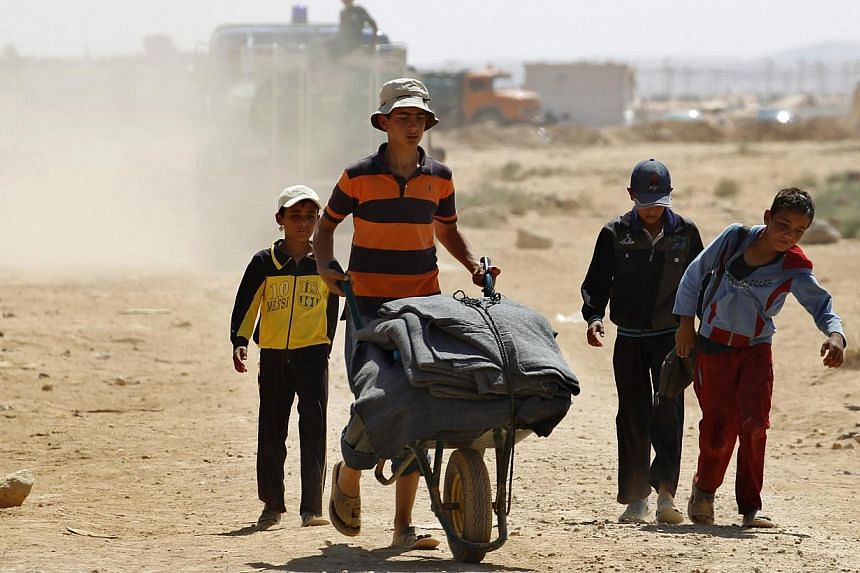Young Syrian refugees transport supplies received from humanitarian organisations to sell outside of Al-Zaatri refugee camp in the Jordanian city of Mafraq, near the border with Syria Sept 1, 2013. -- FILE PHOTO: REUTERS