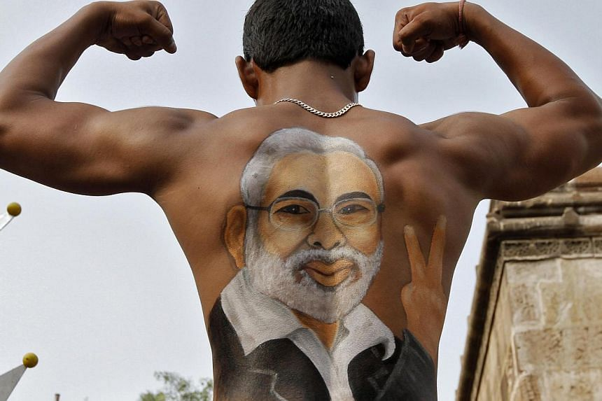 A devotee shows his back, with an image of hardliner Narendra Modi, chief minister of the economically thriving Gujarat state, as he flexes his muscles during a chariot procession in Ahmedabad. India's business community strongly supports Mr Modi to
