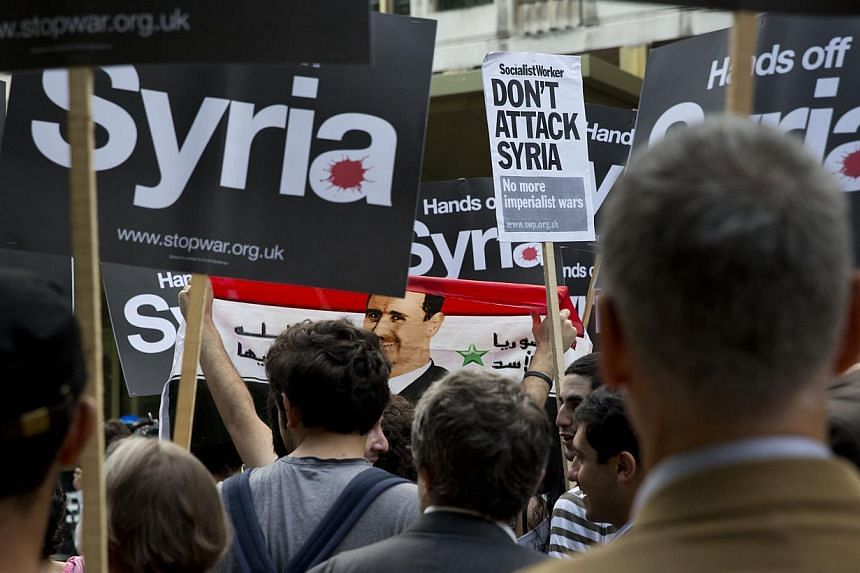 A demonstrator holds a Syrian flag bearing an image of Syrian President Bashar Assad during a protest organised by the Stop the War coalition against any US military intervention in Syria, outside the US embassy in London, on Tuesday, Sept 3, 2013. T