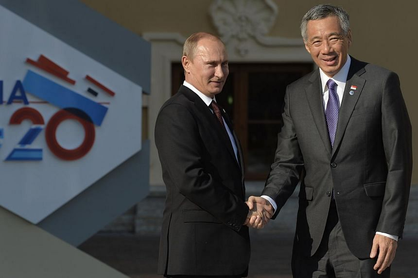 Russia's President Vladimir Putin (left) welcomes Singapore's Prime Minister Lee Hsien Loong at the start of the G20 summit on Sept 5, 2013 in Saint Petersburg. Turmoil in the financial markets might be an immediate concern, but the need to generat