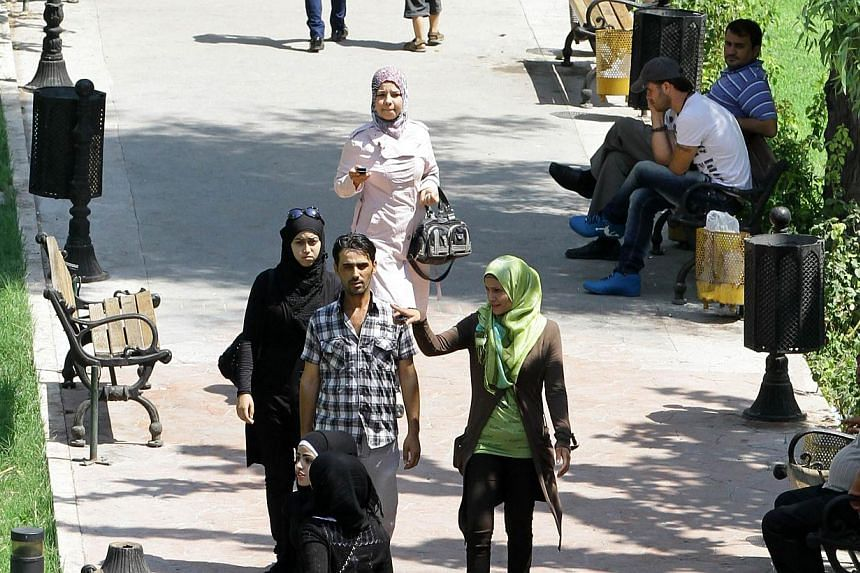 Syrians walk in a park in the capital, Damascus on Sept 5, 2013. As the prospect of US-led strikes looms high over Syria, many residents of Damascus have packed up and fled, some leave it to fate and others defiantly insist their city will not fall.