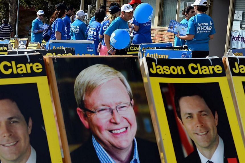 Representatives of different parties with leaflets wait for voters in front of a pre-poll voting centre on election eve in Sydney on Sept 6, 2013. Australian Prime Minister Kevin Rudd refused to concede defeat on Friday despite a new poll showing he
