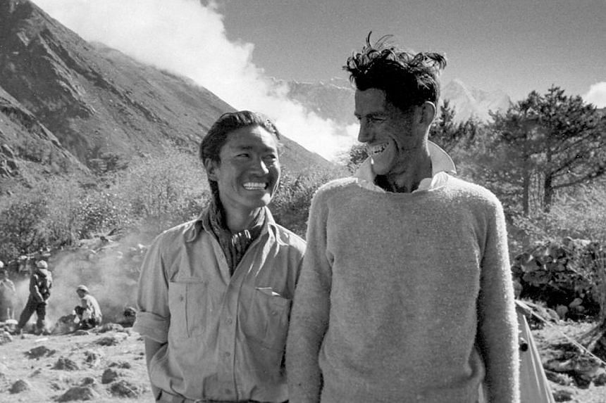 Sir Edmund Hillary (right) and Sherpa Tenzing Norgay smile after their legendary ascent of Mount Everest (summit to the right of Hillary's head) at camp in Thyangboche, Nepal, during the first interview with both men after their quest with Reuters sp