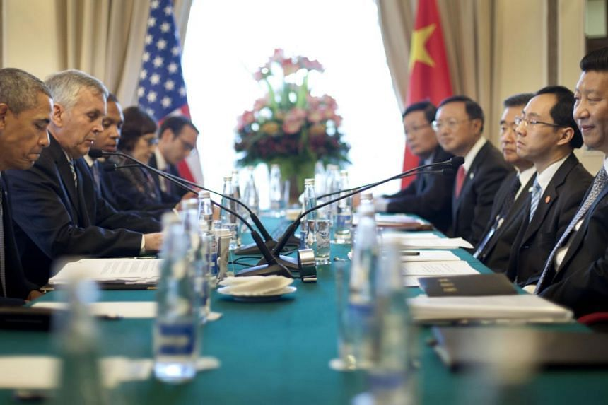 US President Barack Obama (left), China's President Xi Jinping (right) and members of their delegations attend their bilateral meeting at the G-20 Summit on Friday, Sept 6, 2013 in St Petersburg, Russia. MrXi told Mr Obama on Friday that the cr