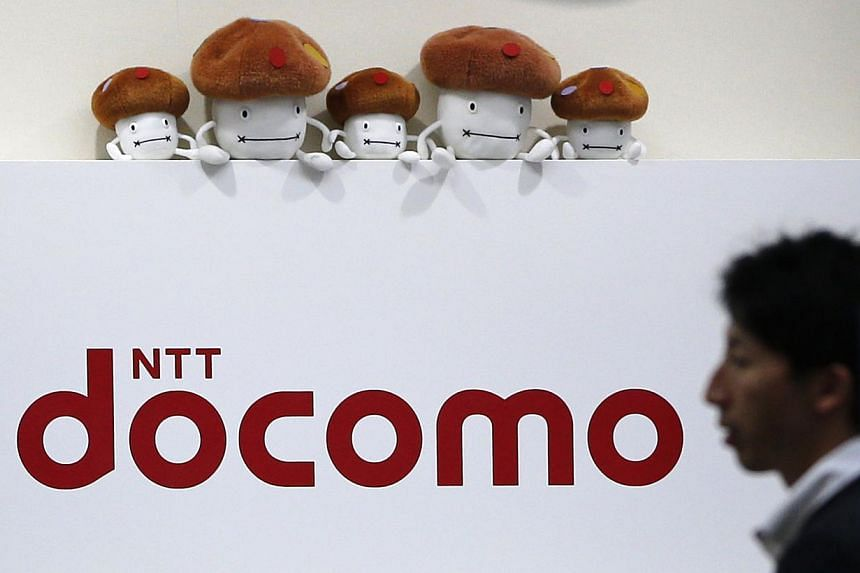 A man walks past the logo of Japan's biggest mobile phone operator NTT DoCoMo at its shop in Tokyo on July 3, 2013. DoCoMo is expected to start selling iPhones as soon as autumn, helping Apple extend its reach in a country where it has more than
