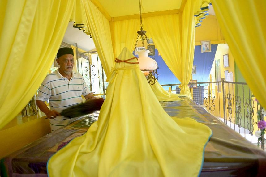 (Above) Mr Zainol Atan, 60, looks after the shrine of Princess Radin Mas Ayu at the foot of Mount Faber. Next door is one of several black-and-white bungalows that have been gazetted as heritage buildings. -- ST PHOTO: LIM SIN THAI
